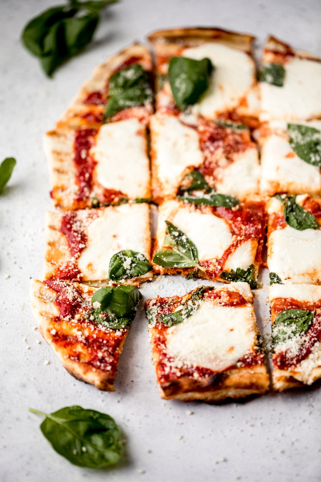 grilled pizza with cheese and basil cut into squares