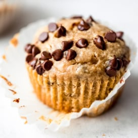 peanut butter banana muffins with chocolate chips on a grey surface