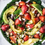 avocado strawberry spinach salad in a bowl with red onion, feta, almonds and pistachios