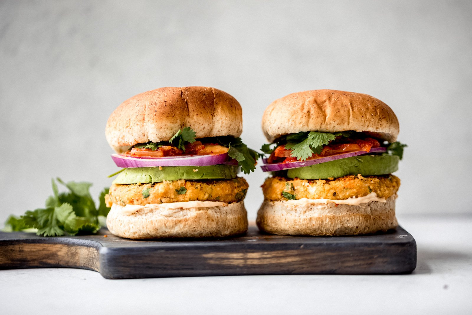 two vegan sweet potato burgers on a wooden cutting board