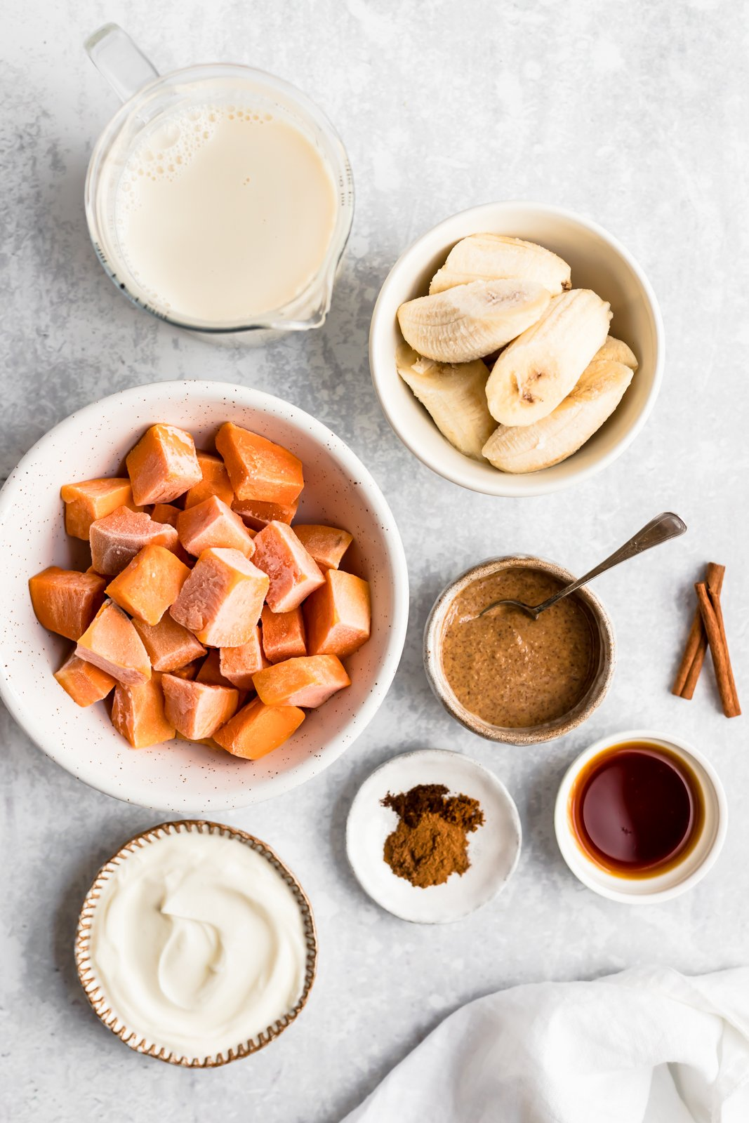 sweet potato smoothie ingredients laid out in bowls in a surface