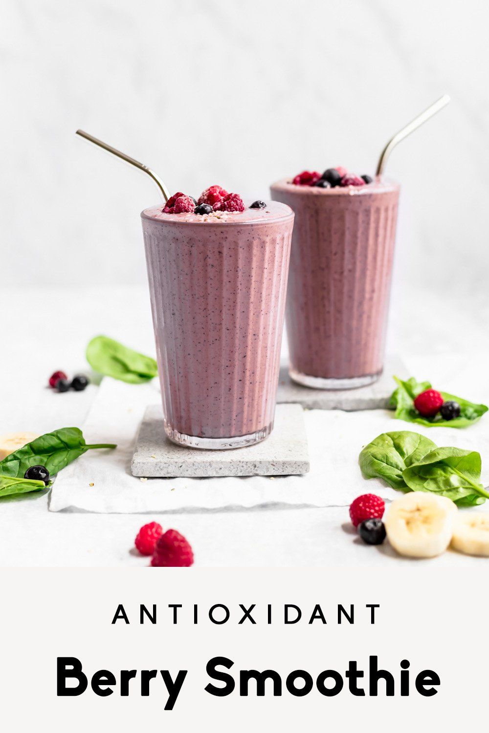 two berry smoothies in glasses topped with raspberries and blueberries