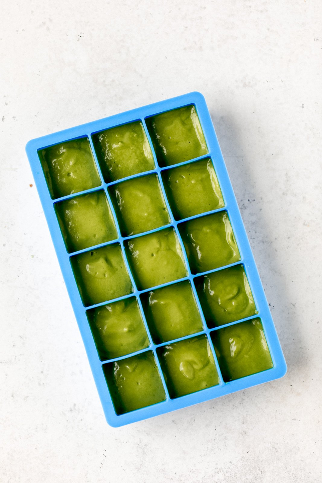 ice cube tray with green smoothie in it