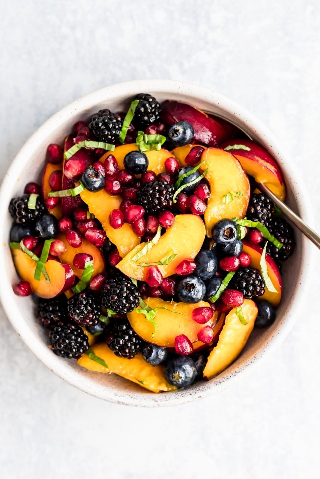 summer peach fruit salad in a bowl with basil ribbons