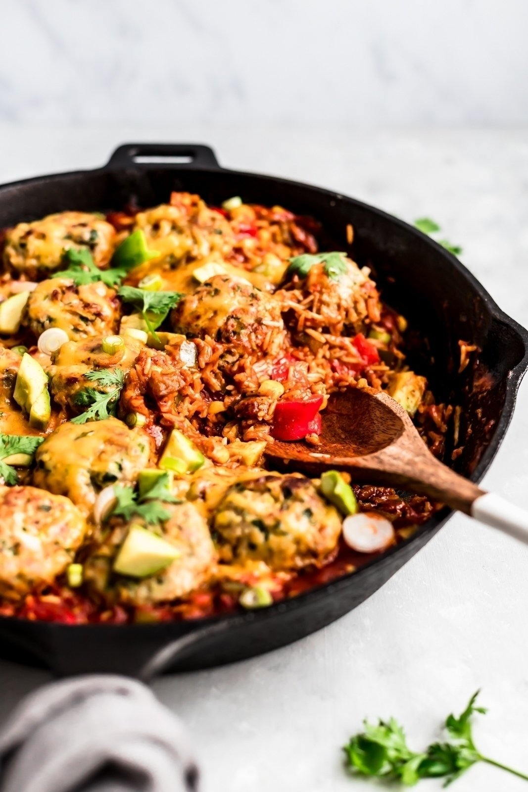 zucchini turkey meatballs with rice, veggies and cheese in a skillet with a wooden spoon