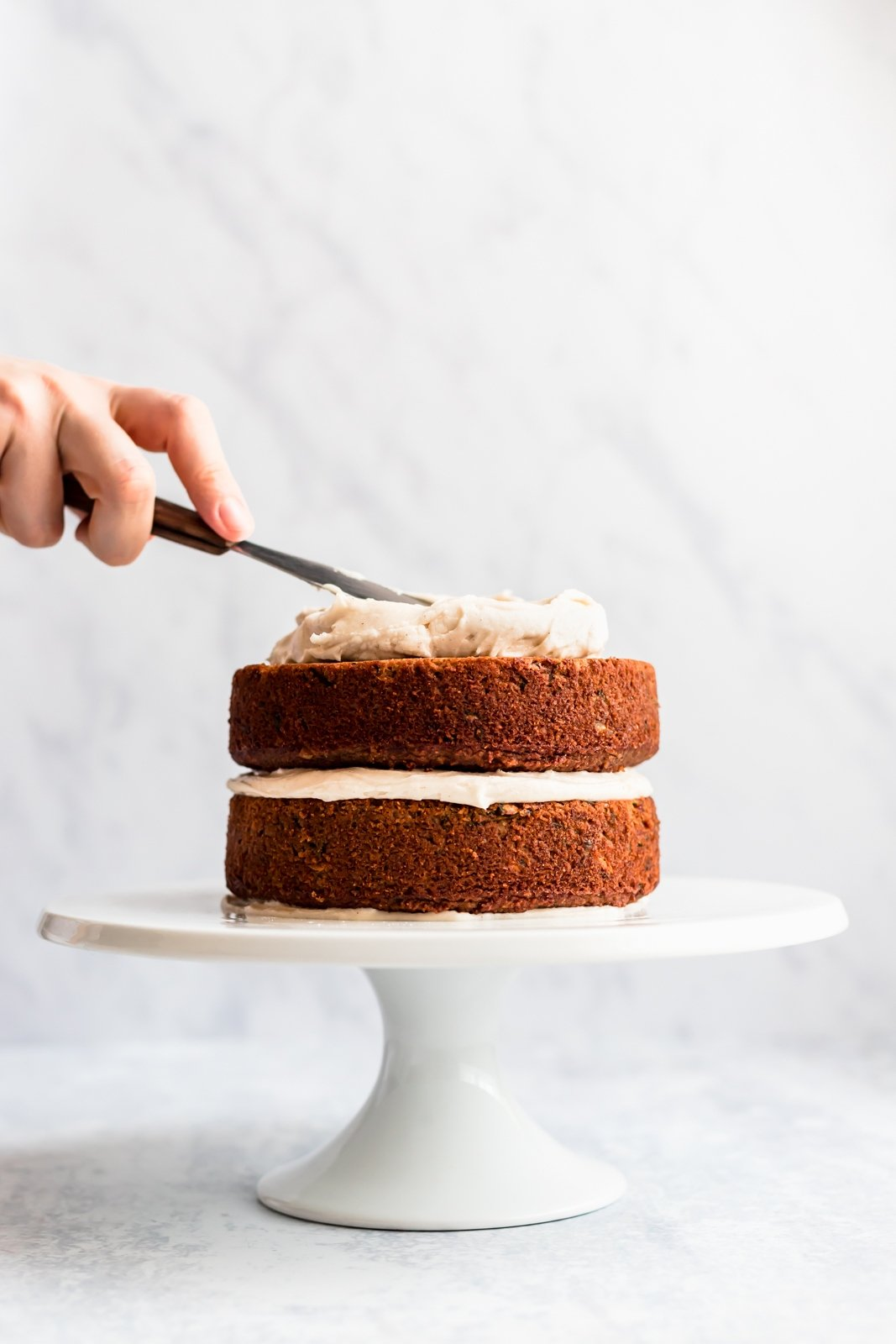 zucchini sweet potato cake on a cake stand with cream cheese frosting being put on