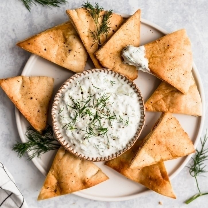 homemade tzatziki sauce in a bowl on a plate with pita chips
