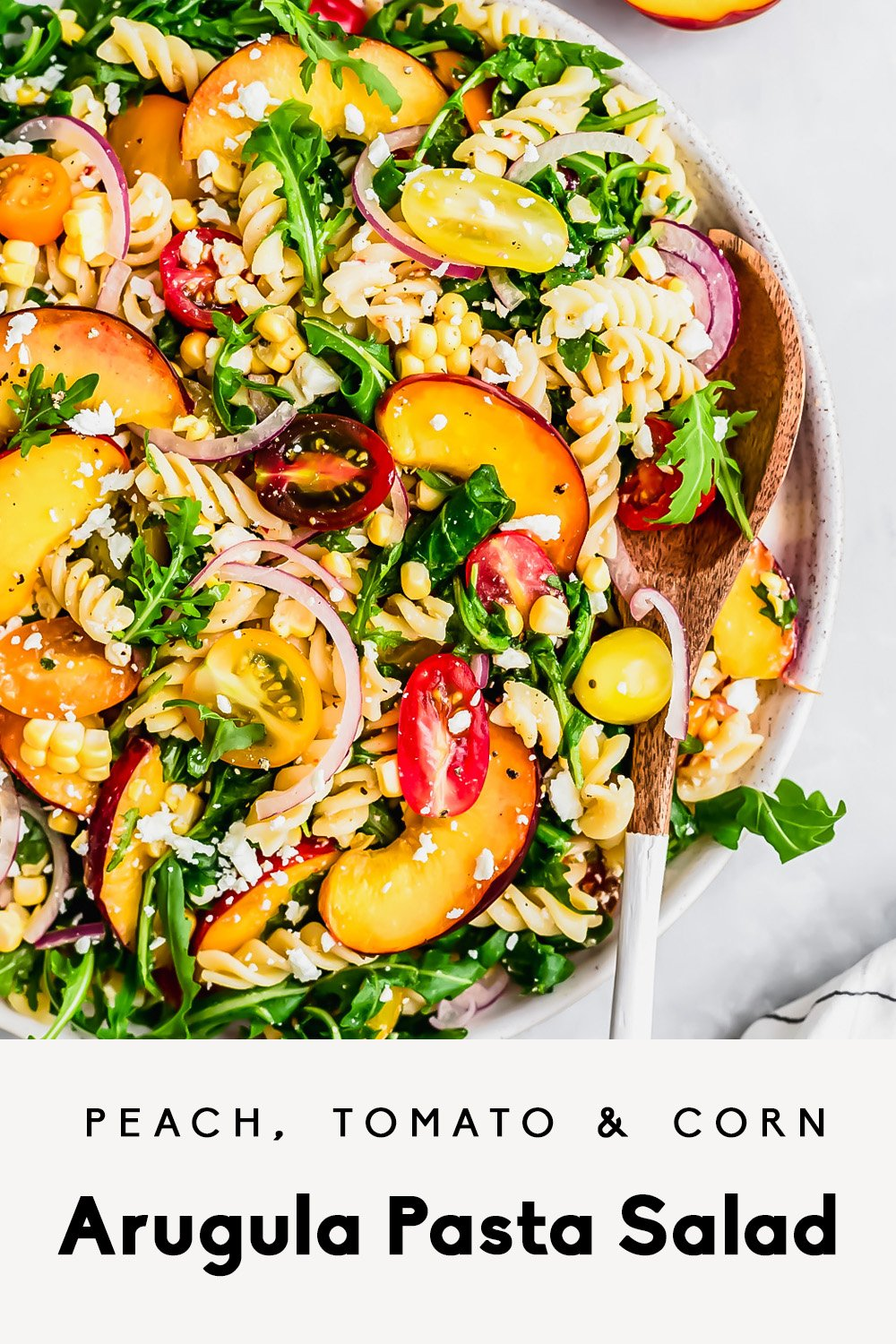 arugula pasta salad with peaches, tomatoes, corn and feta in a bowl