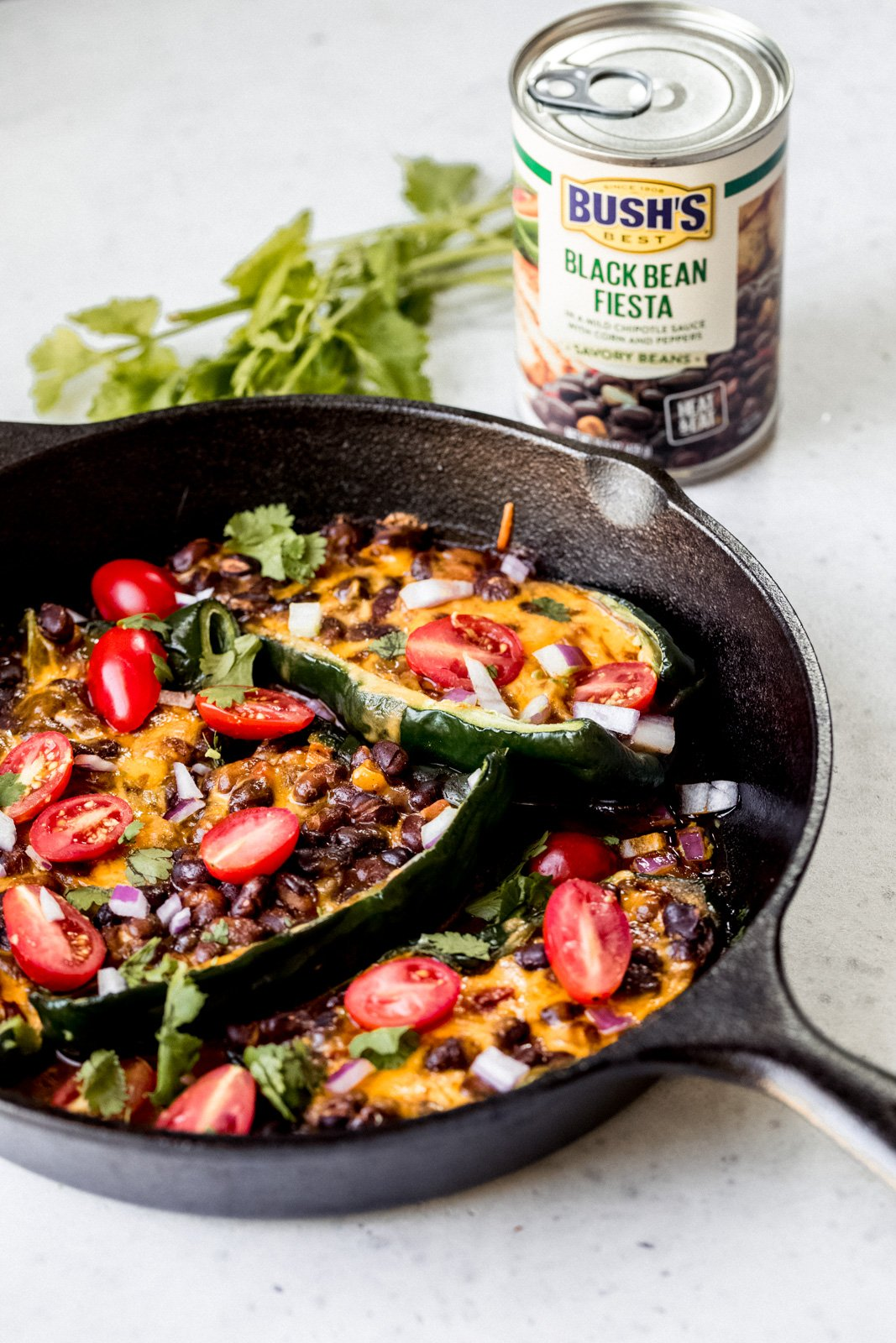 grilled stuffed poblano peppers with beans and cheese in a skillet next to a can of beans