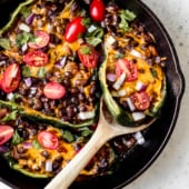 grilled stuffed poblano peppers in a skillet with a wooden spoon
