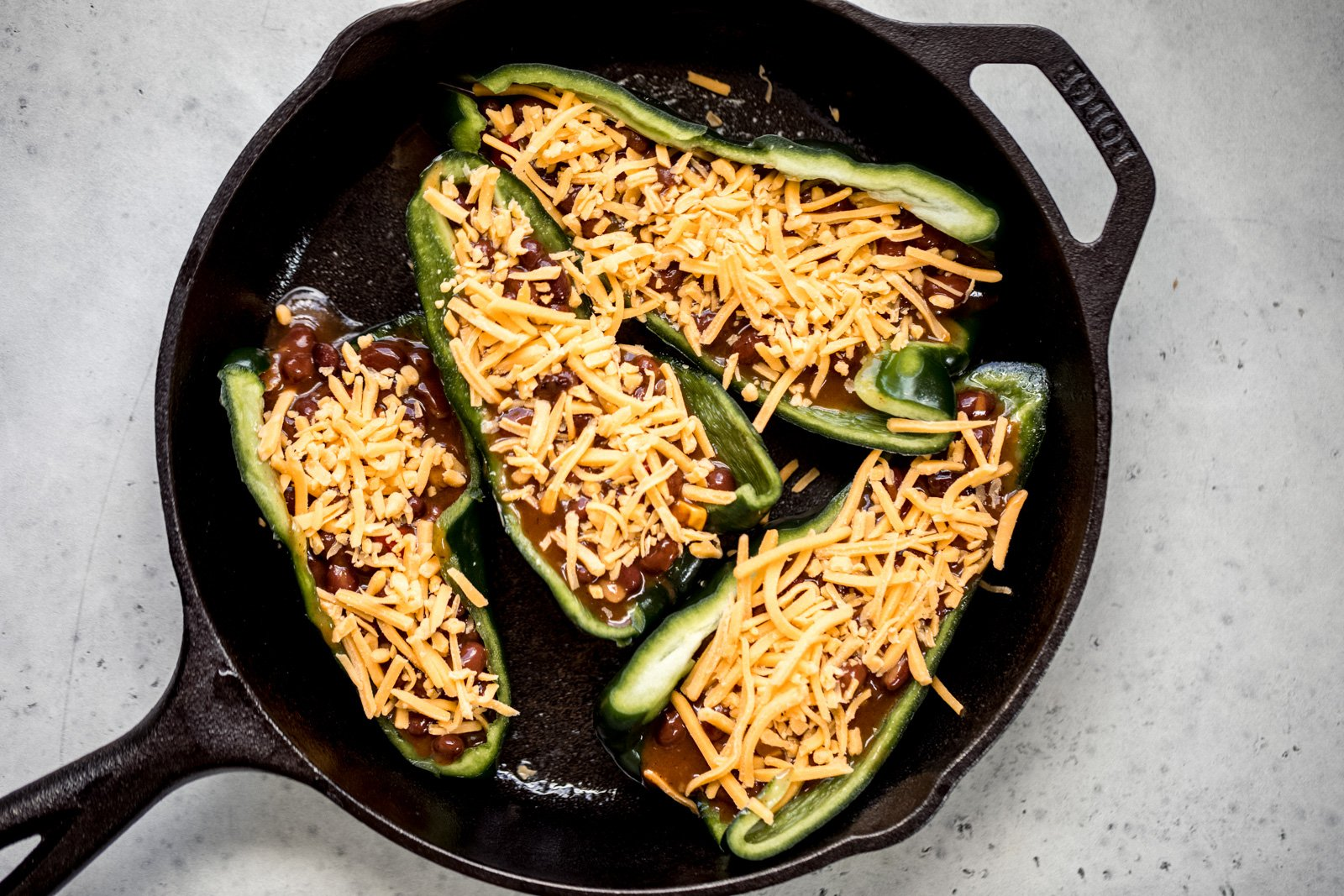 stuffed poblano peppers with beans and cheese in a cast iron skillet