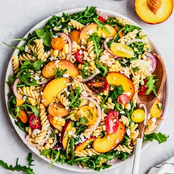 arugula pasta salad with peaches in a bowl