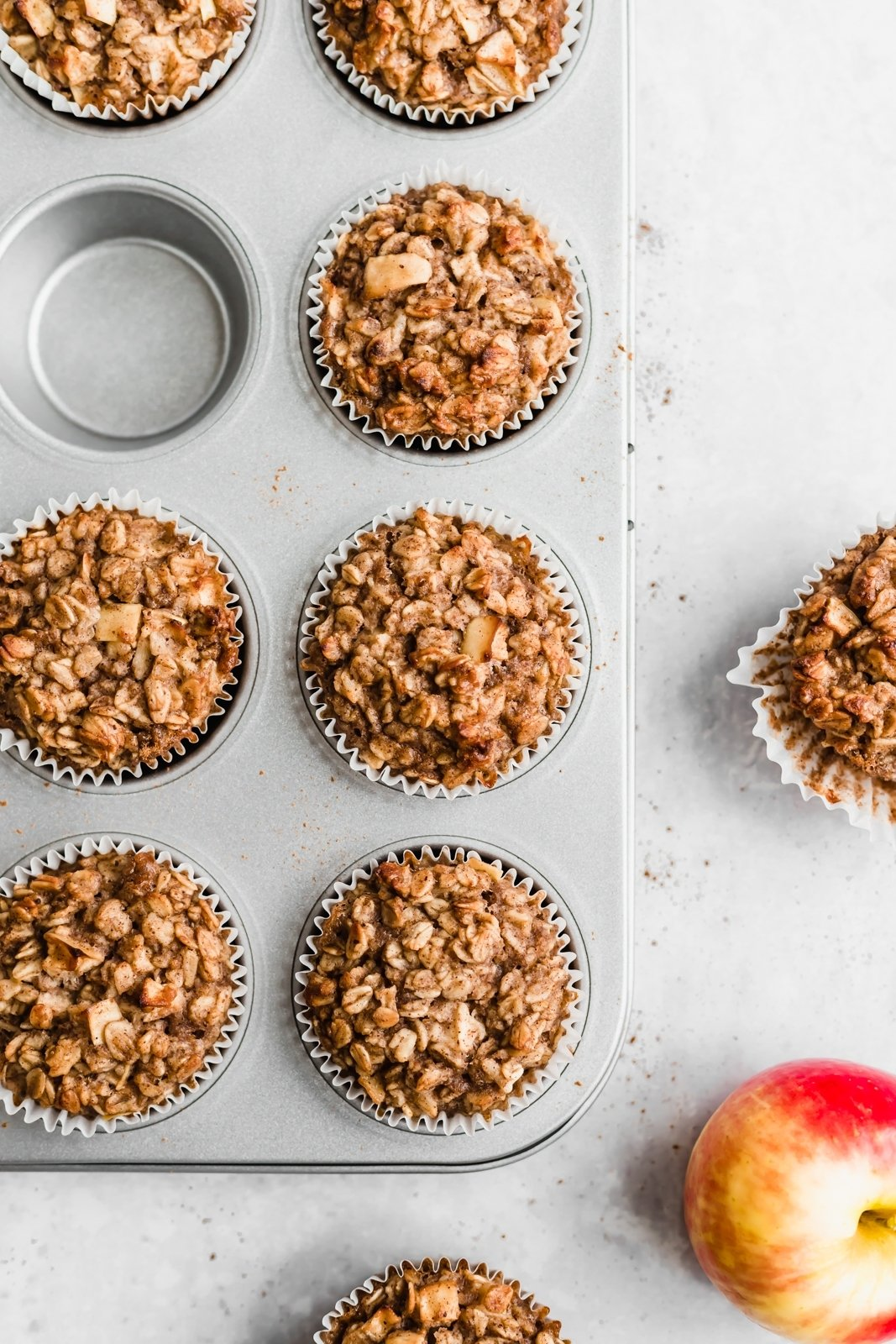 apple cinnamon baked oatmeal cups in a muffin tin