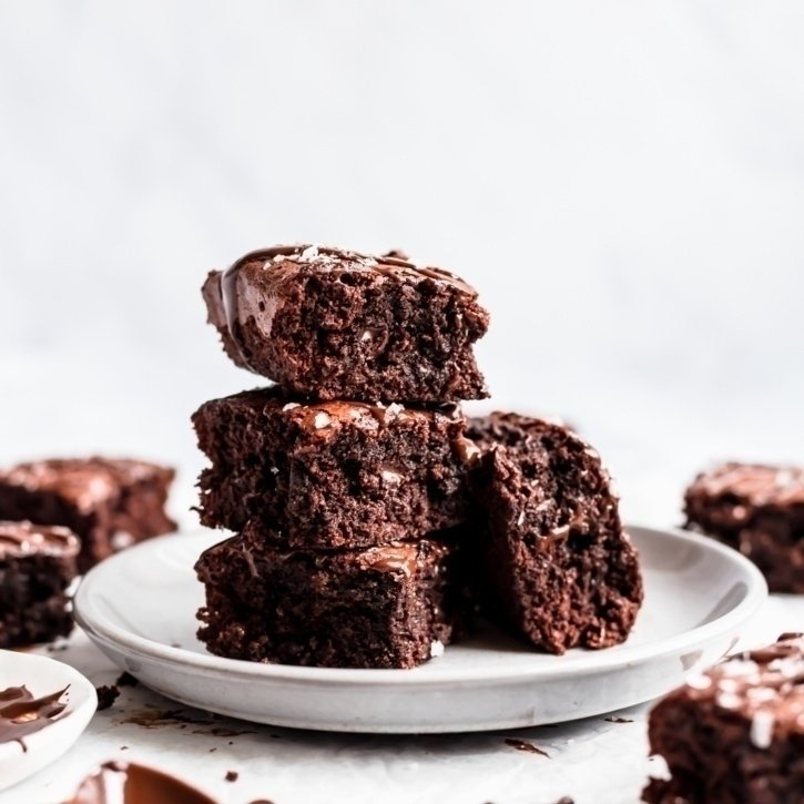flourless almond butter brownies in a stack on a plate