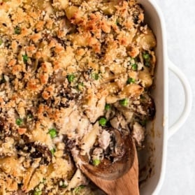 healthy tuna noodle casserole in a pan with a wooden spoon