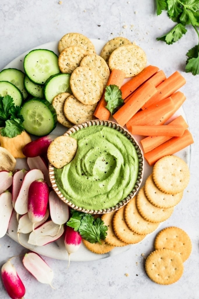 spicy green cashew dip in a bowl on a platter with veggies and crackers