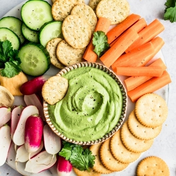 spicy green cashew dip on a platter with veggies and crackers