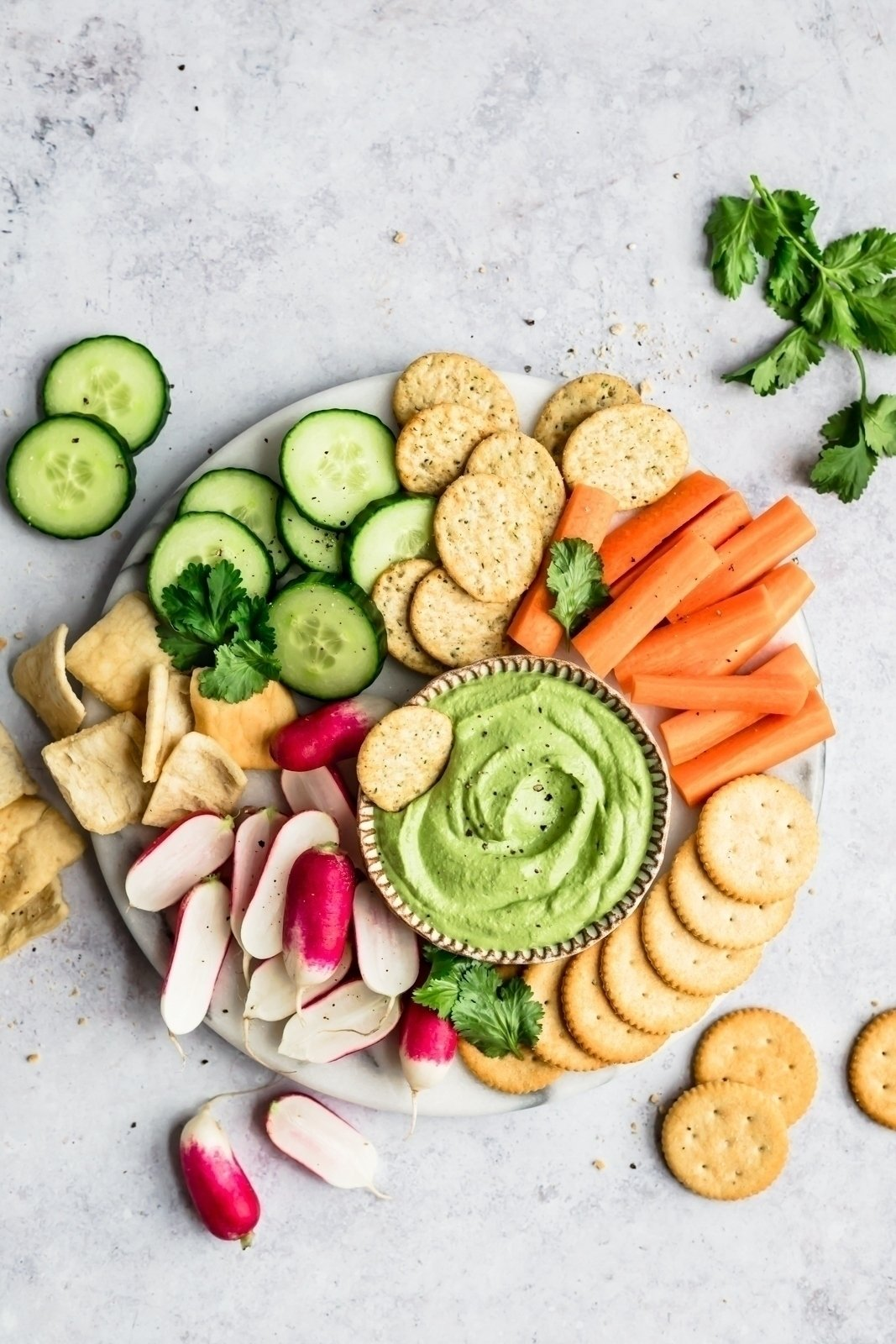 spicy green vegan cashew dip on a platter with veggies and crackers