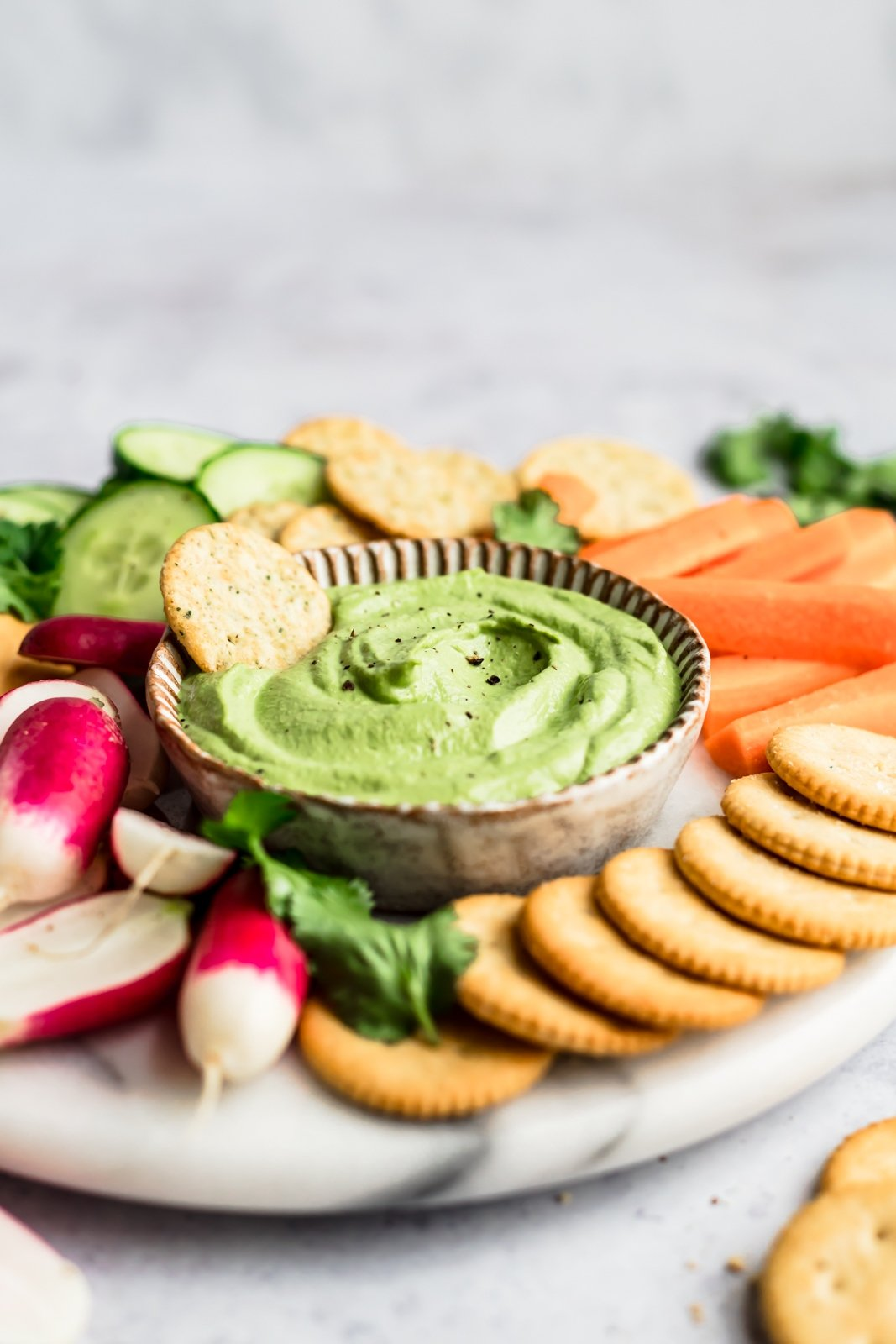 spicy green cashew dip on a platter with a cracker in it