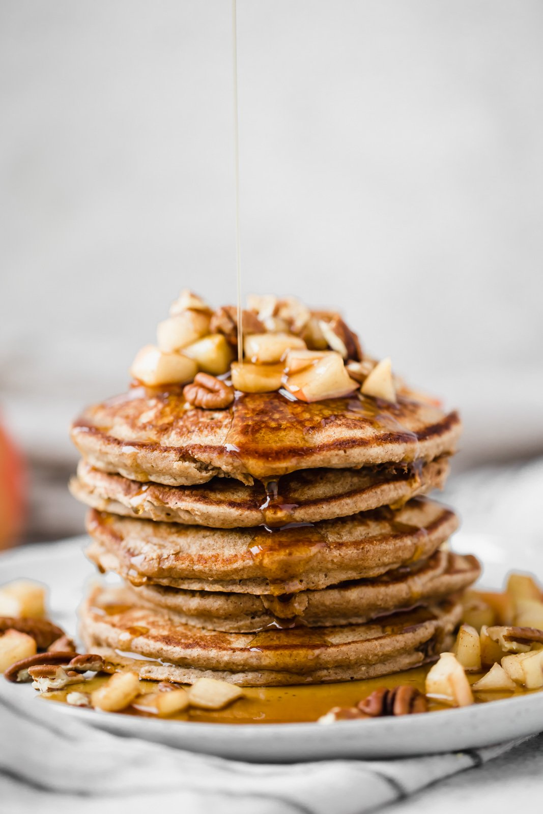 healthy apple pancakes on a plate with maple syrup being poured on top