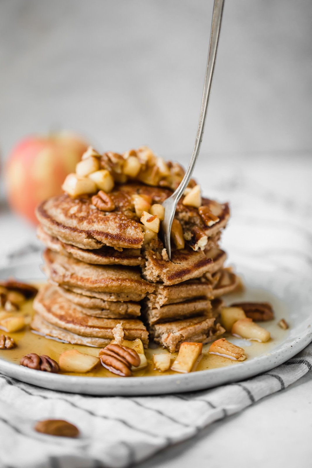 healthy apple pancakes on a plate with a fork removing pancakes