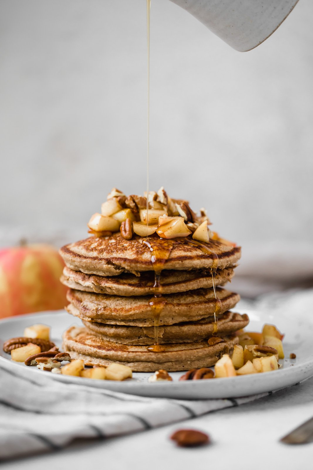 healthy apple pancakes with maple syrup being poured on top