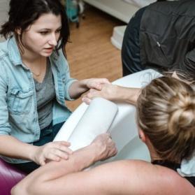 doula helping a woman in a bathtub