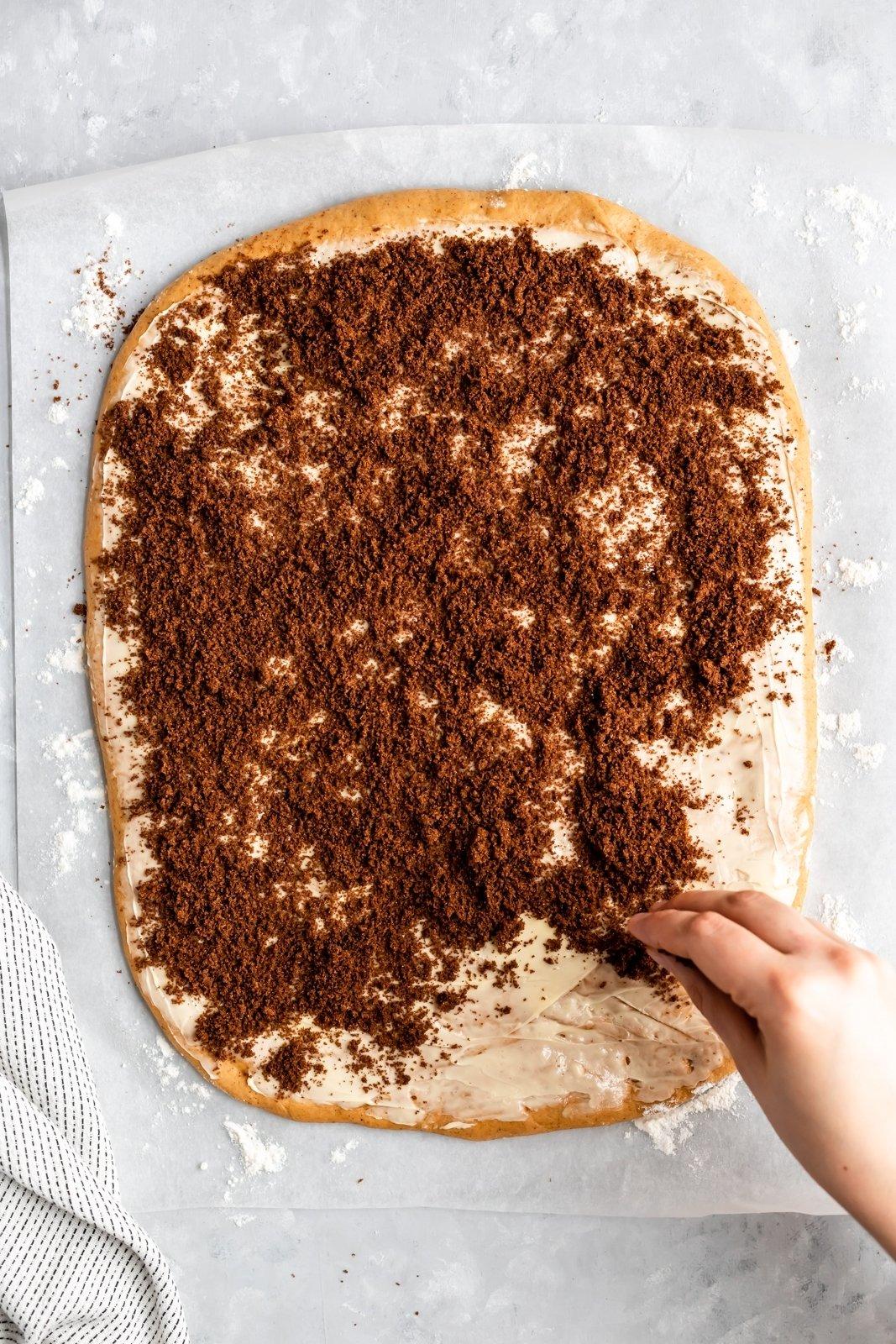 brown sugar being sprinkled on pumpkin cinnamon roll dough