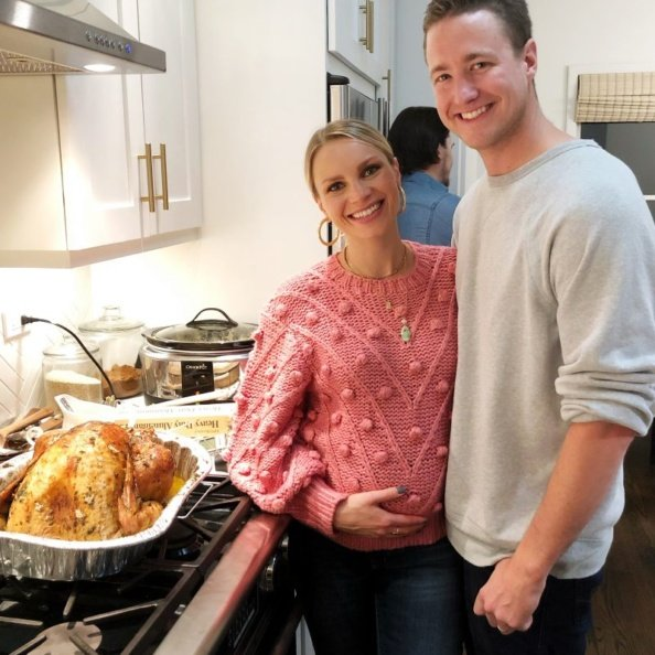 monique and tony in the kitchen in front of a thanksgiving turkey