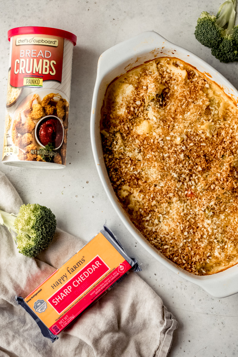cheddar broccoli cauliflower gratin in a baking dish next to a block of cheddar and bread crumbs