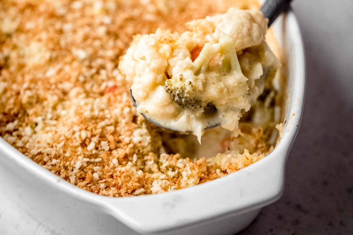 scooping a spoonful of broccoli cauliflower gratin out of a baking dish