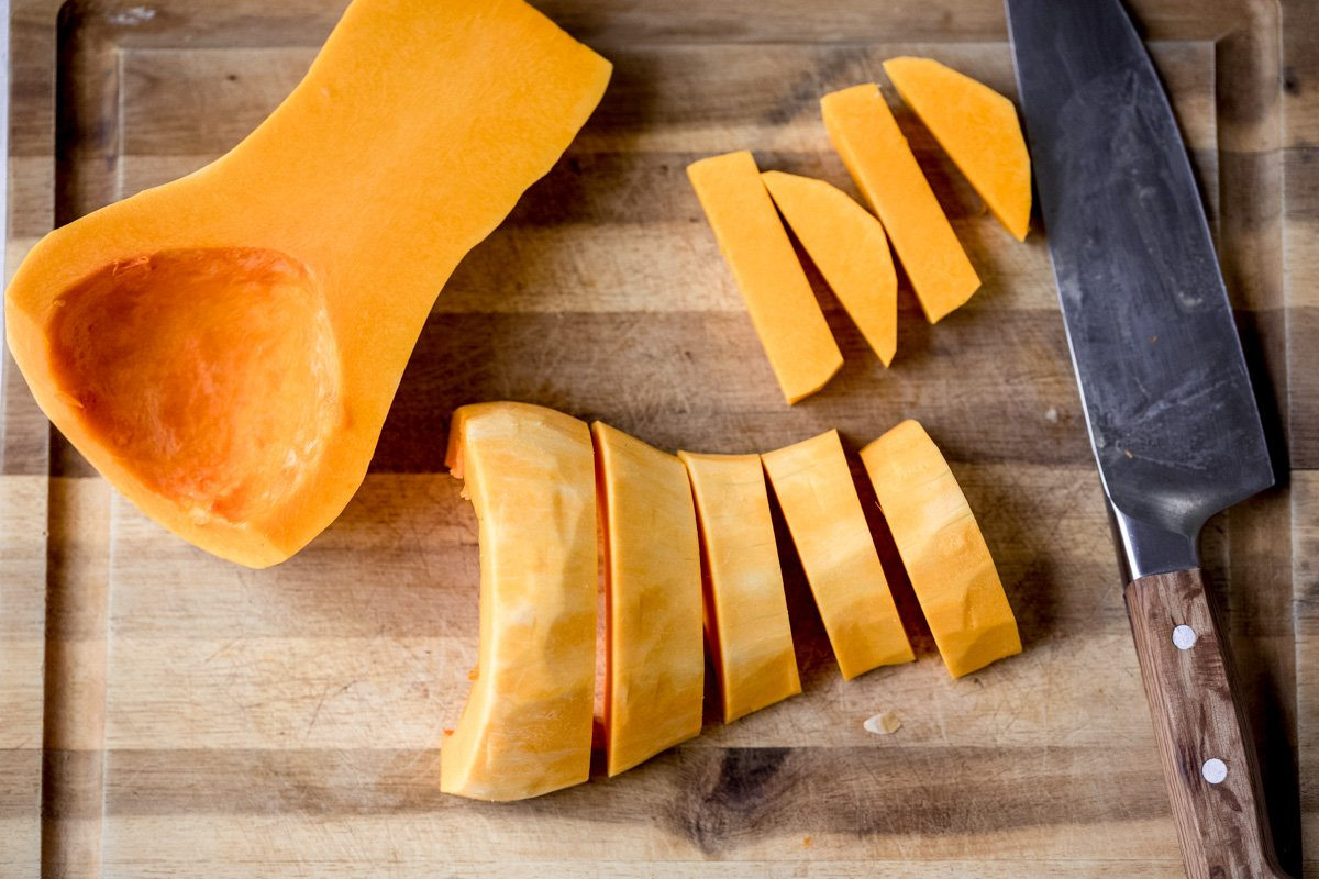 butternut squash being cut into slices and cubes