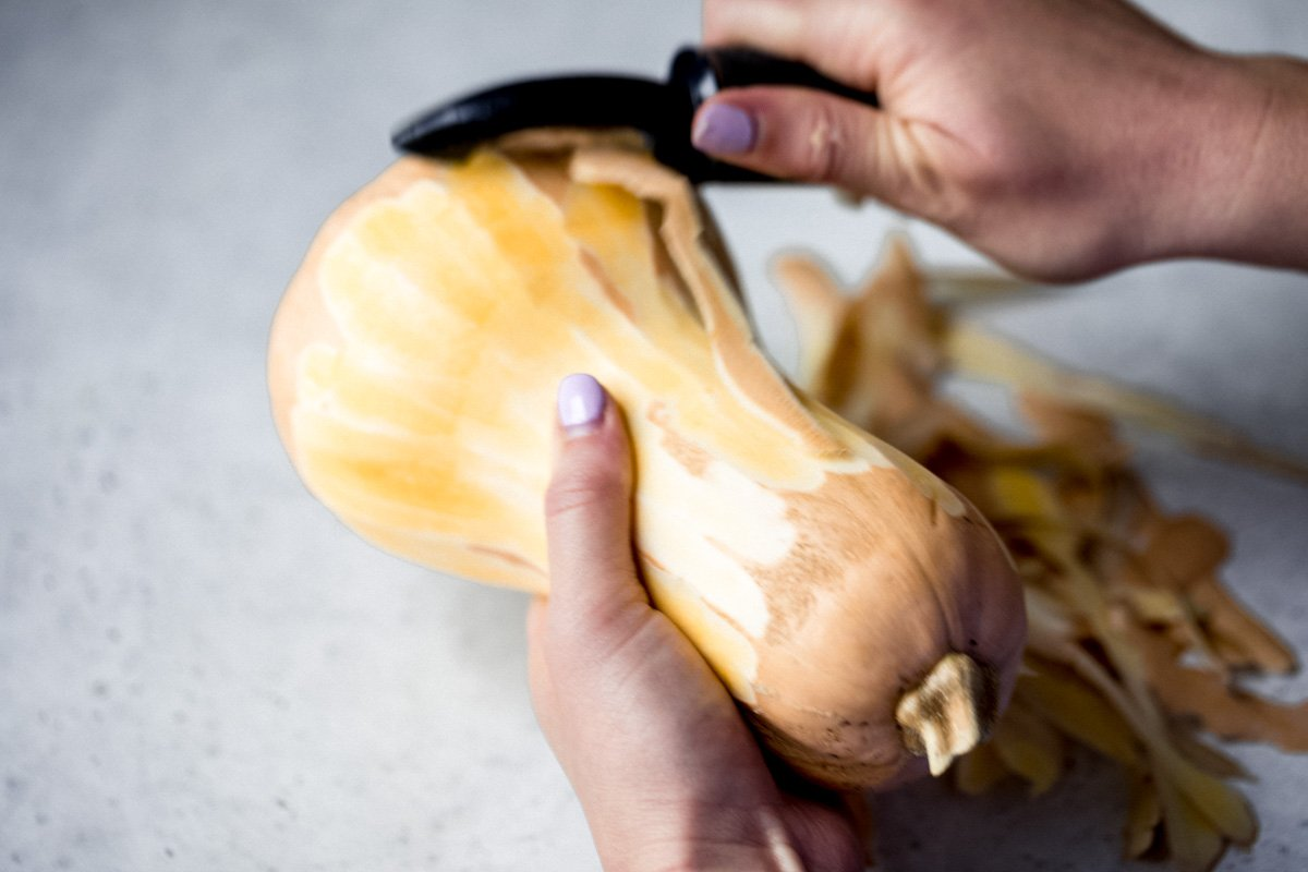 hands using a vegetable peeler to peel a butternut squash