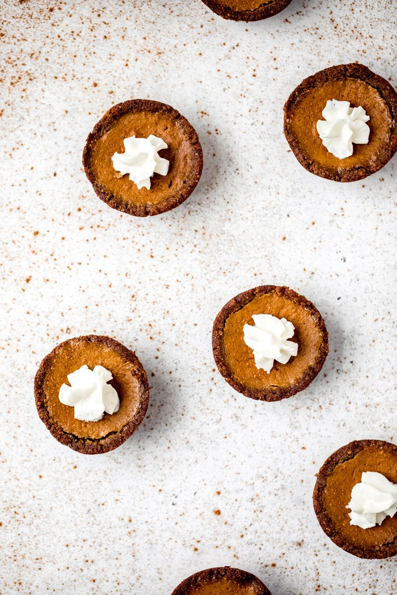 mini pumpkin pies with whipped cream on a surface