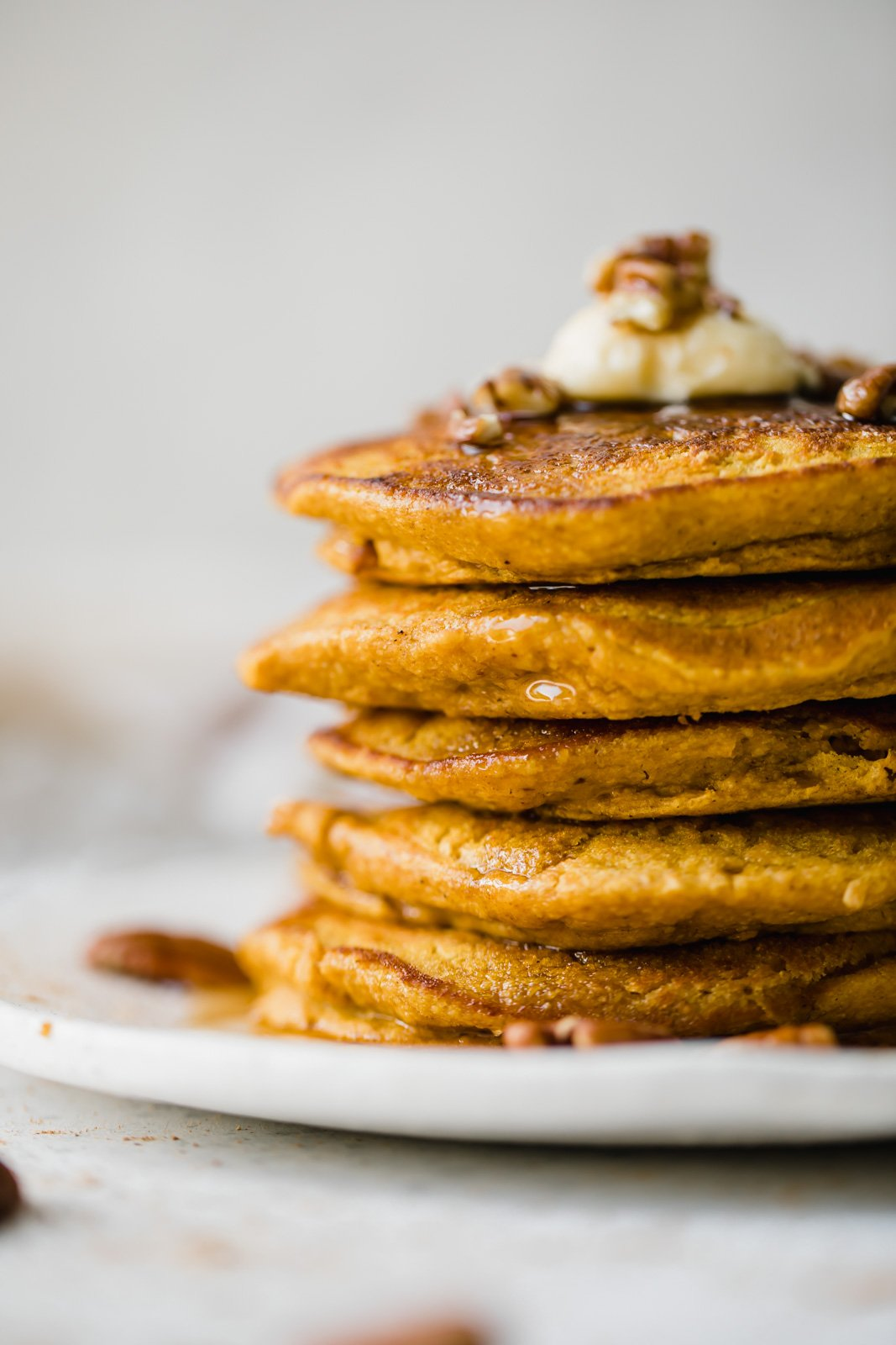stack of healthy pumpkin pancakes on a plate with maple syrup