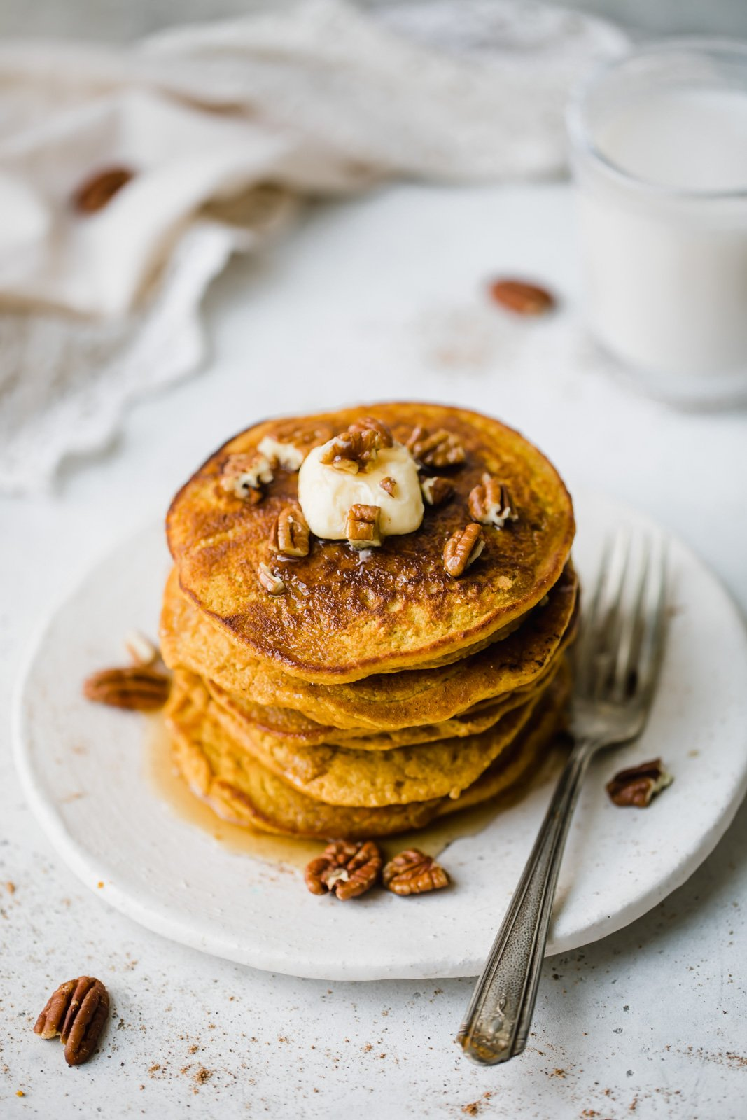 healthy pumpkin pancakes stacked on a plate with a fork on the side