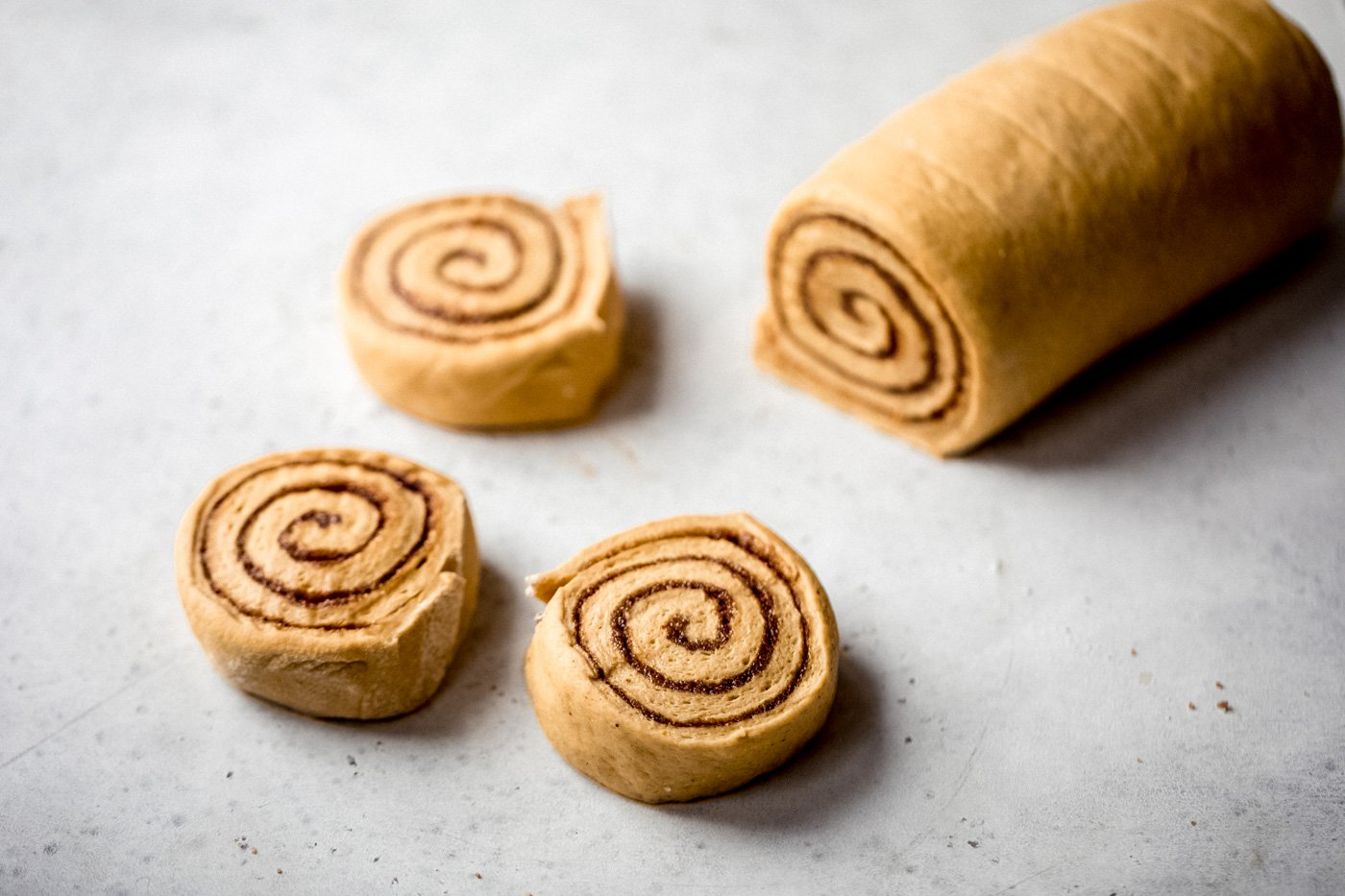 pumpkin cinnamon roll dough being cut