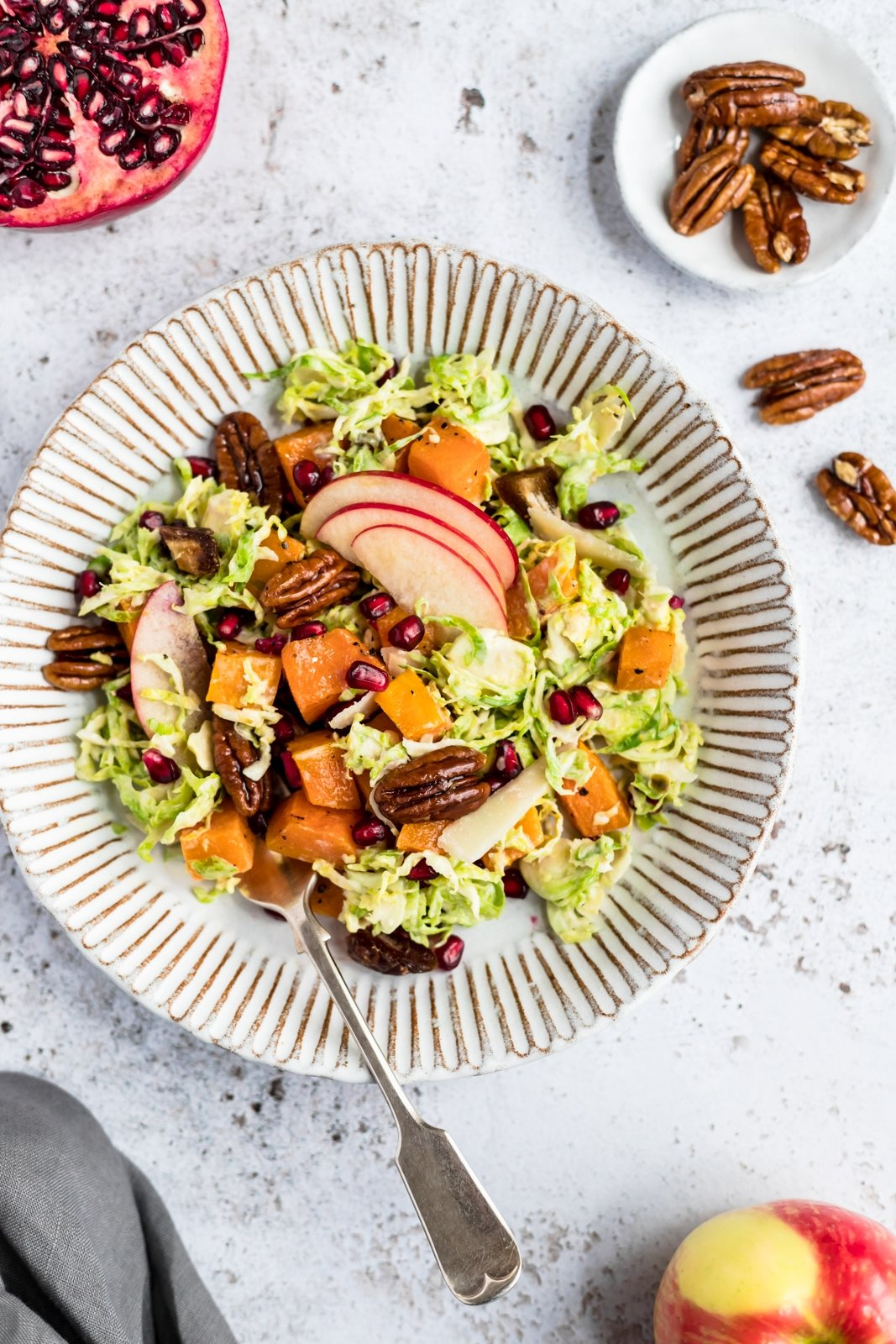 brussels sprouts caesar salad with apples and butternut squash on a plate