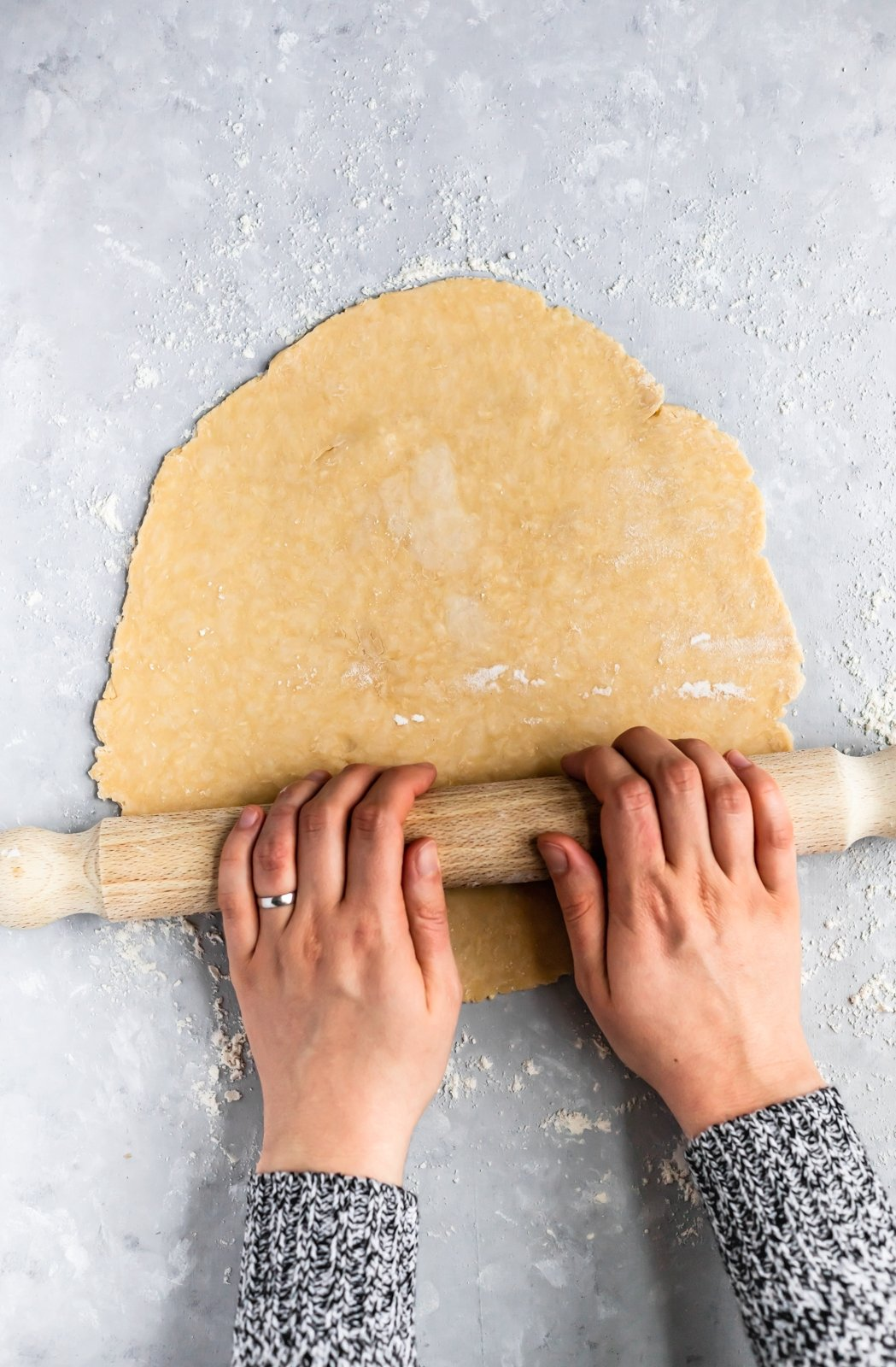 two hands using a rolling pin to roll out all butter pie dough