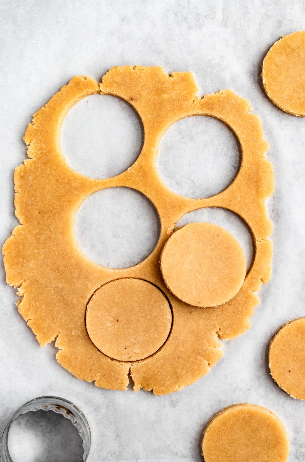 gluten free shortbread being cut into shapes for fudge striped cookies