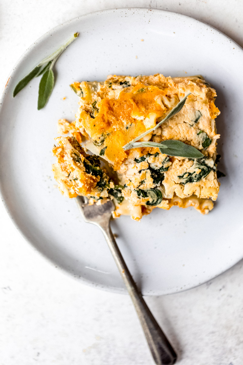 slice of vegan butternut squash lasagna on a plate with a fork
