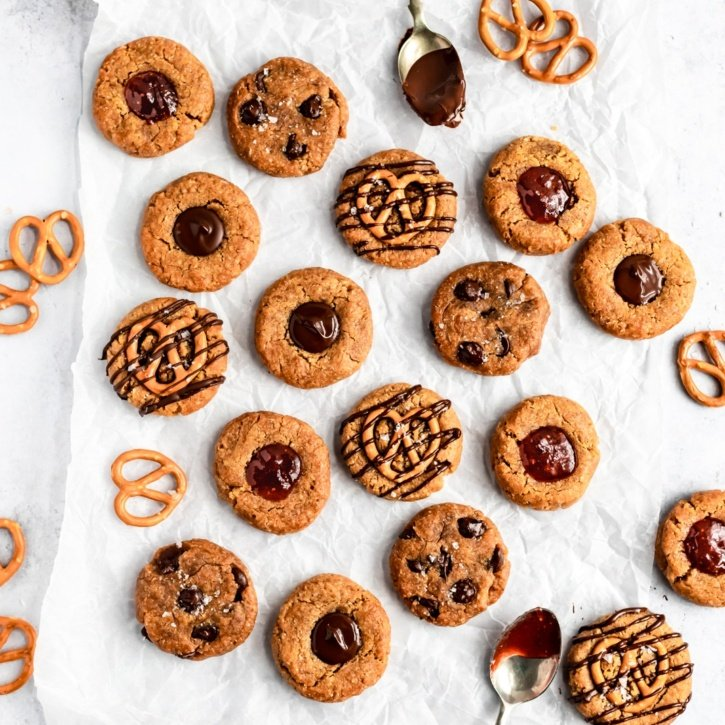 vegan peanut butter cookies on parchment paper with toppings