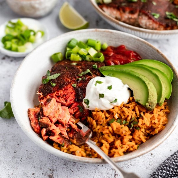 healthy salmon taco bowl topped with avocado and greek yogurt