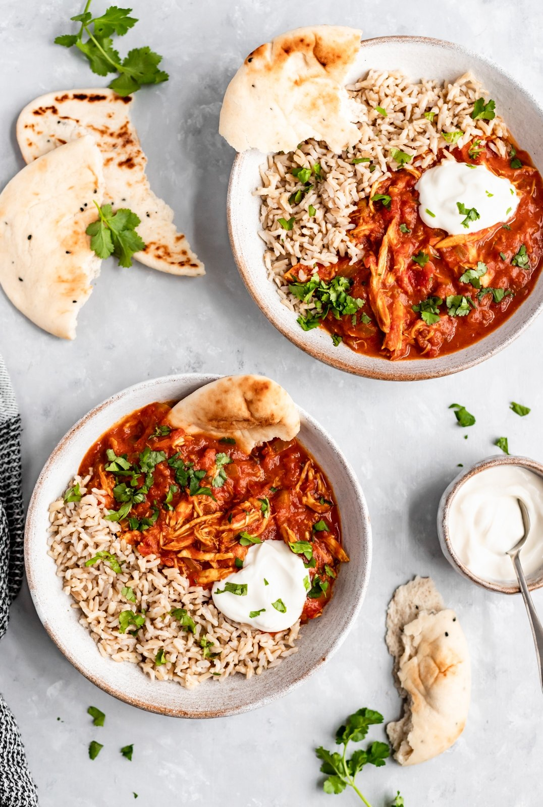 two bowls of slow cooker chicken tikka masala with brown rice