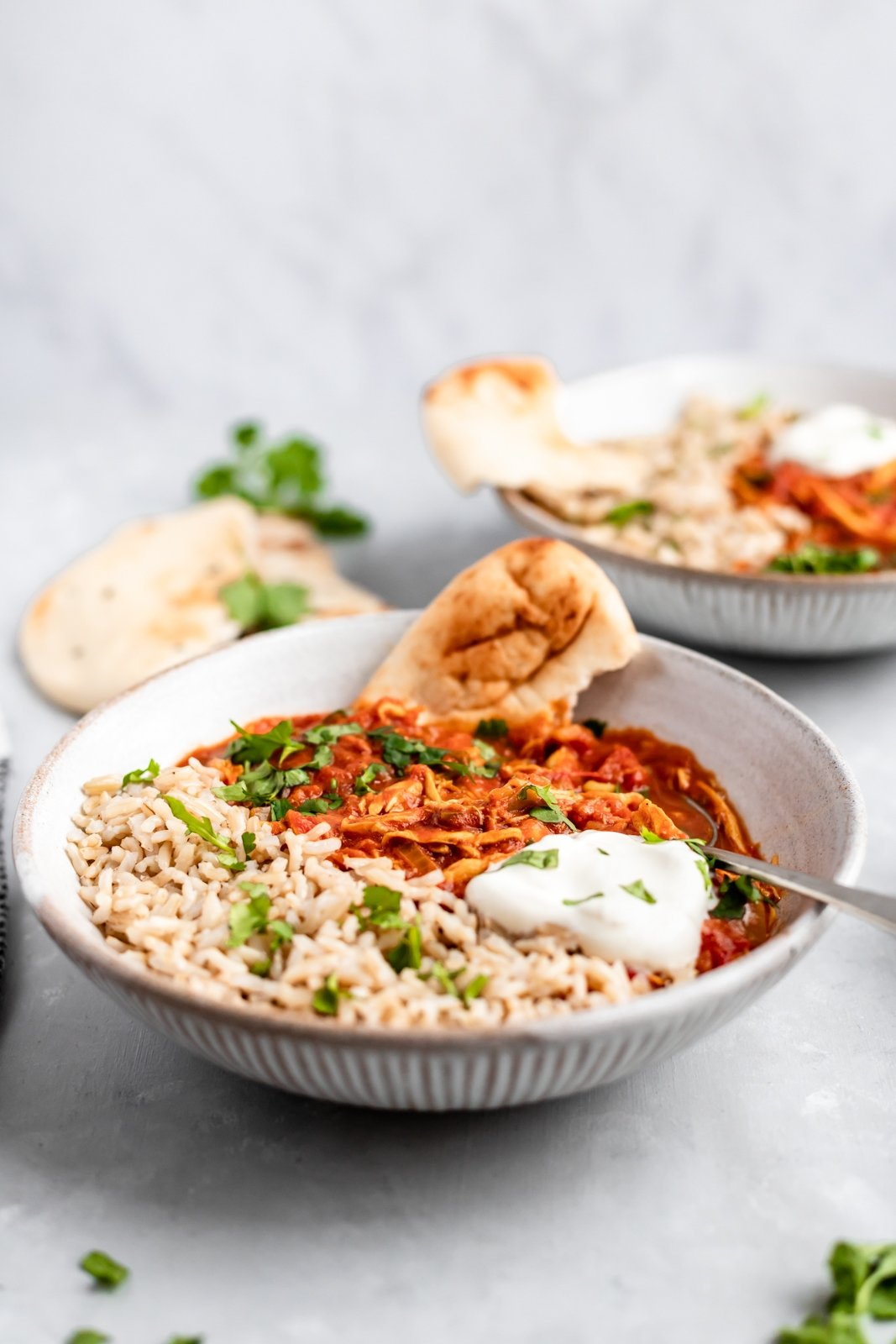 slow cooker chicken tikka masala in a bowl with naan and brown rice