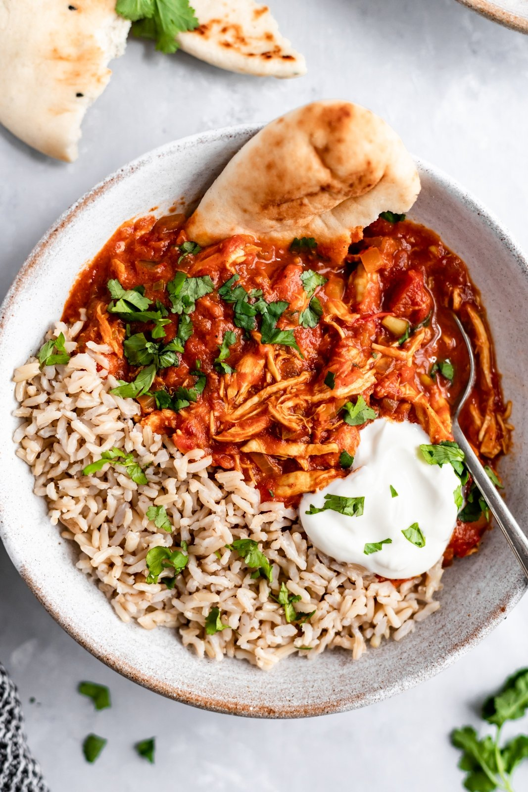 slow cooker chicken tikka masala in a bowl with brown rice, naan and yogurt