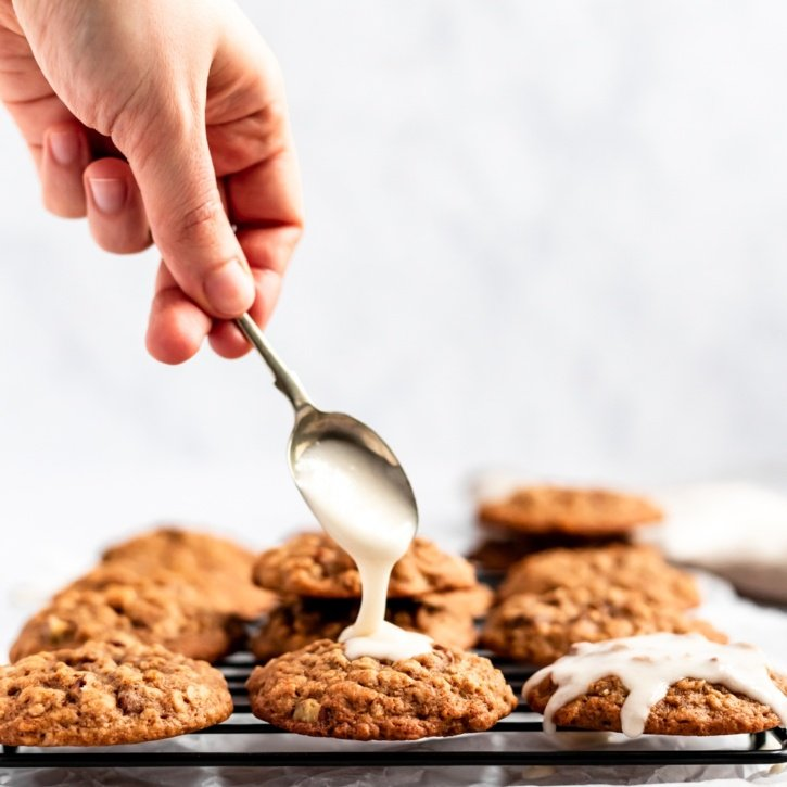 maple pecan oatmeal cookies being topped with a salted maple icing