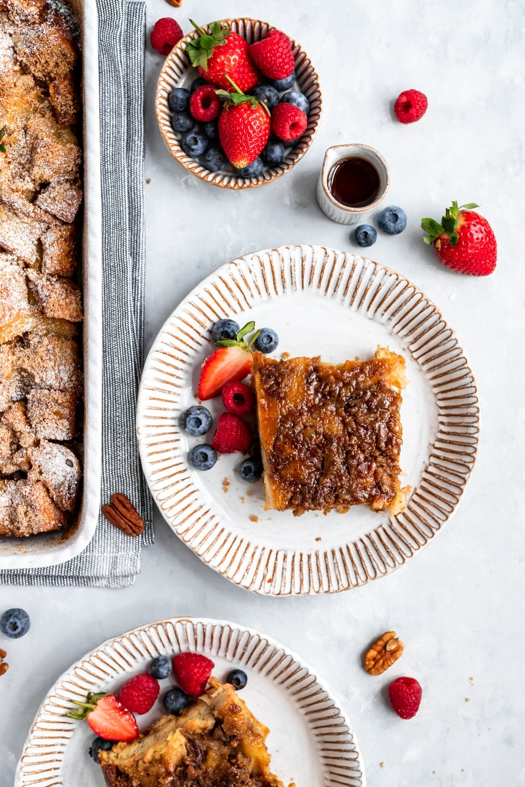 overnight french toast casserole on a plate with berries on the side