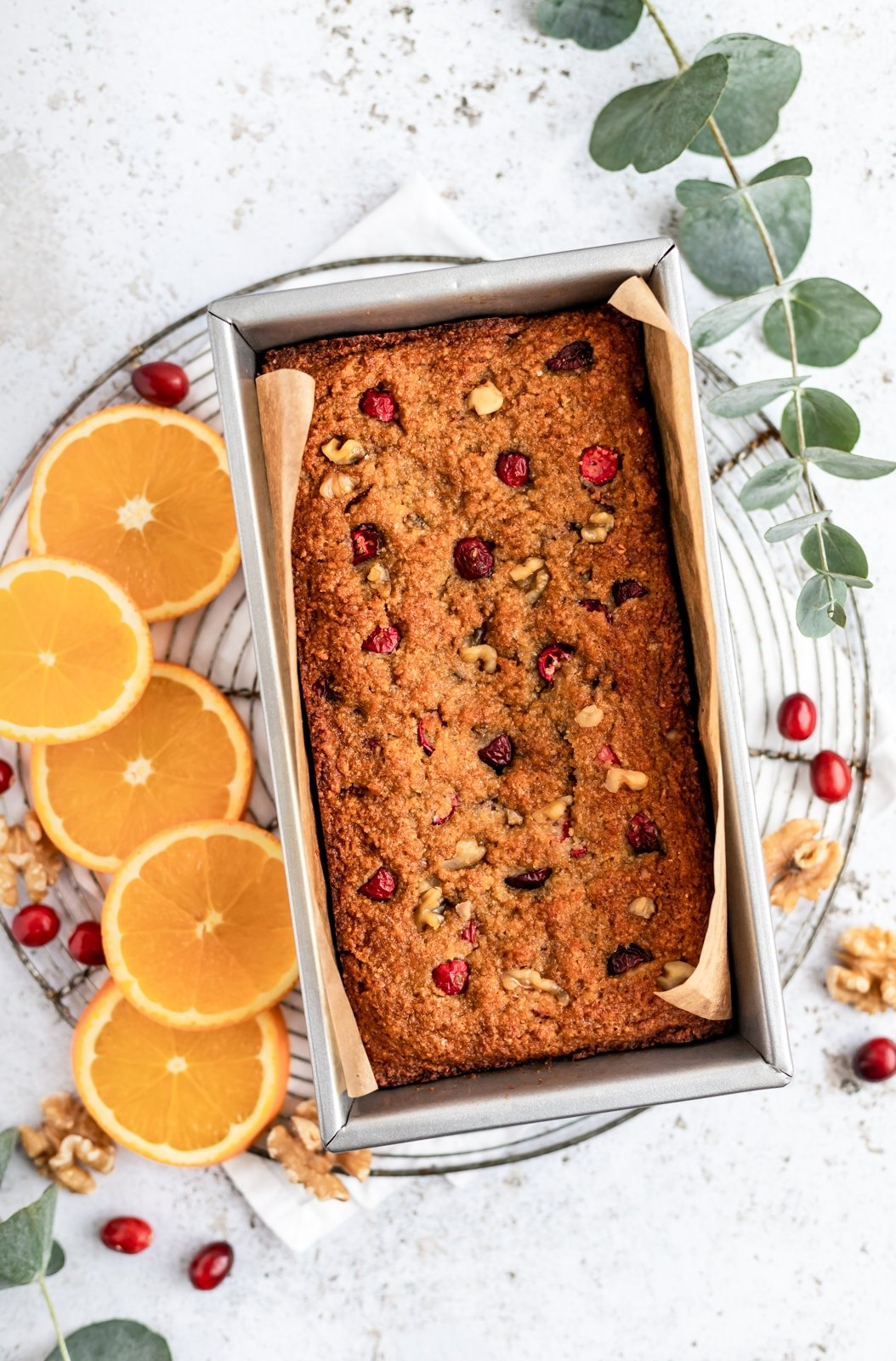 paleo orange cranberry bread in a bread pan on a cooling rack