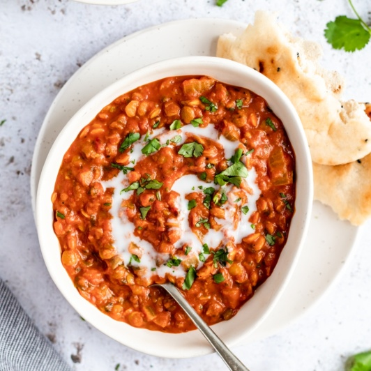 vegan tomato lentil soup in a bowl with naan